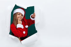 Little girl in santa clothes breaking out of paper Stock Images