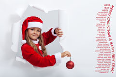 Little girl in santa costume leaning out of torn edges hole in p Stock Photos