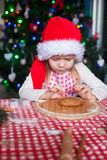 Little girl in Santa hat baking gingerbread Royalty Free Stock Photos