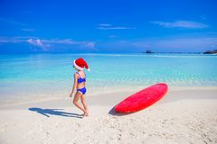 Little girl in Santa hat on the beach during Stock Photos
