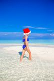 Little girl in Santa hat on the beach during Stock Images
