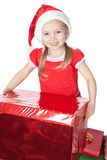 Little girl in santa hat with big red gift on whit Stock Image