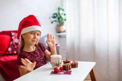 Little girl in Santa hat with Christmas ginger cookies and cup of cacao with marshmallow royalty free stock photography