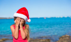 Little girl in santa hat covering her face Stock Photo