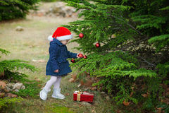Little girl in Santa hat decorates a Christmas tree in the forest. Xmas holiday concept. Christmas composition with a little girl Royalty Free Stock Image