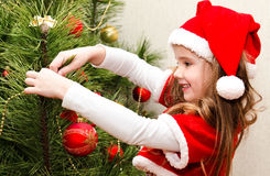 Little girl in santa hat decorating the christmas tree Stock Images
