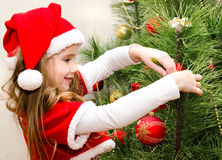 Little girl in santa hat decorating the christmas tree Royalty Free Stock Images