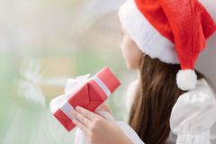 Little girl in Santa hat dreaming by the window holding gift Royalty Free Stock Images
