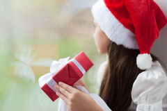 Little girl in Santa hat dreaming by the window holding gift Stock Photography