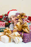 Little girl in Santa hat with gift box for Christmas. Stock Photos