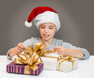 Little girl in Santa hat with gift box for Christmas. Royalty Free Stock Photo