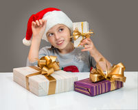 Little girl in Santa hat with gift box for Christmas. Royalty Free Stock Image