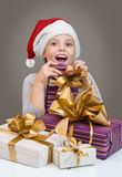 Little girl in Santa hat with gift box for Christmas. Royalty Free Stock Photos