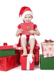 Little girl in santa hat with gifts on white Royalty Free Stock Photo