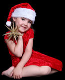 Little girl in Santa hat with golden star. Stock Photos