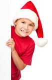 Little girl in santa hat is holding blank board Royalty Free Stock Photos