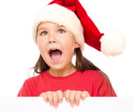 Little girl in santa hat is holding blank board Stock Image