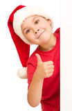 Little girl in santa hat is holding blank board Royalty Free Stock Photo