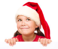 Little girl in santa hat is holding blank board Stock Photos