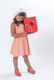 Little girl in a Santa hat is holding Christmas gift royalty free stock photo
