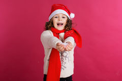 Little girl in santa hat is holding fake snow royalty free stock photography