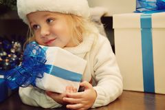 Little girl in santa hat holding a gift. Cute little girl in santa hat lying under the Christmas tree and holding a gift. xmas kid Royalty Free Stock Photo