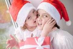 Two cute little girls with Christmas gifts. Little girl in Santa hat kissing older girl with Christmas gift Royalty Free Stock Photography