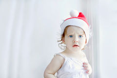 Little girl in santa hat, on a light background near the window Stock Photography