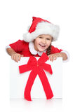 Little girl in Santa hat looks out of gift box. Portrait of happy little girl in Santa hat looks out of Christmas gift box, on a white background Royalty Free Stock Photography