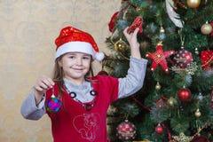 Little girl in Santa hat near Christmas tree Stock Photography