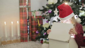 Little girl in santa hat opening Christmas gift. stock video footage