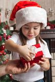 Little girl in Santa hat opens red gift box for Christmas in fat Stock Photos