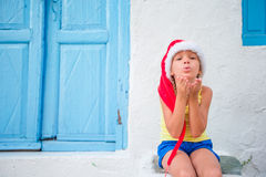 Little girl in santa hat outdoors in old street on Christmas vacation in Mykonos. Kid at street of typical greek Royalty Free Stock Photo