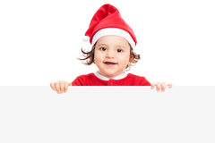 Little girl with Santa hat posing behind panel Royalty Free Stock Images