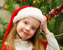 Little girl in santa hat with present have a christmas Stock Images
