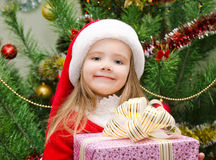 Little girl in santa hat with present have a christmas Royalty Free Stock Photos
