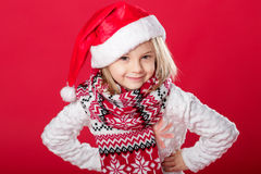 Little girl in santa hat and scarf on red background Stock Images