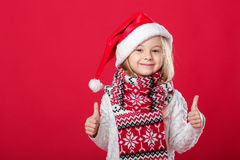 Little girl in santa hat and scarf on red background Stock Image
