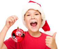 Little girl in santa hat is showing thumb up sign Royalty Free Stock Photo