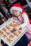 Little girl in Santa hat shows her Christmas Royalty Free Stock Photography