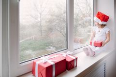 Little girl in Santa hat sits on window sill and holding gift Stock Photo