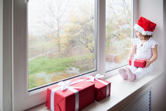 Little girl in Santa hat sits on window sill and holding gift Royalty Free Stock Photos