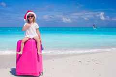 Little girl in Santa hat sitting on a large suitcase at tropical beach Stock Photo