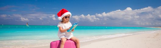 Little girl in Santa hat sitting on large suitcase Stock Image