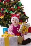 Little girl in Santa hat sitting under Christmas tree royalty free stock image