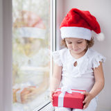 Little girl in Santa hat sitting by the window and holding box with a gift Stock Photos
