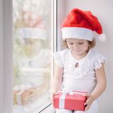 Little girl in Santa hat sitting by the window and holding box w Royalty Free Stock Photo