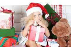 Little girl in santa helper hat with gift Stock Photos