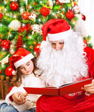 Little girl with Santa read book Royalty Free Stock Images