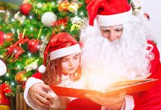 Little girl with Santa read book Stock Photography